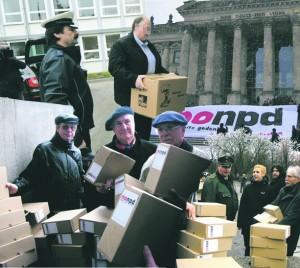 Eine Collage zum NPD-Verbotsantrag. Zu sehen ist der Kurier, der  unter Polizeischutz am 3.12.2013 den NPD-Verbotsantrag der Bundesländer beim Bundesverfassungsgericht einreicht. Die anderen Bilder zeigen Mitglieder der VVN-BdA wie sie beim Bundestag kistenweise Unterschriften für ein NPD-Verbot beim Bundestag in Berlin übergeben.