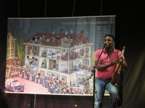 Veranstaltung gegen Rechts im Jugendzentrum von Langen in Hessen. Der eritreischer Musiker Semereab Teklia vor dem Wimmelbild der VVN-Neofaschismus-Ausstellung. Foto: Philipp Schappert